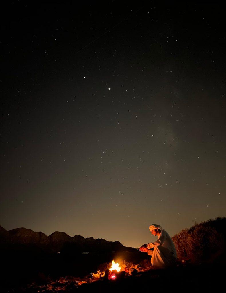   사막의 캠프파이어 앞에 앉은 남성의 야간 사진. 쿠웨이트 압둘라 샤이제가 아이폰12 프로로 촬영했다.